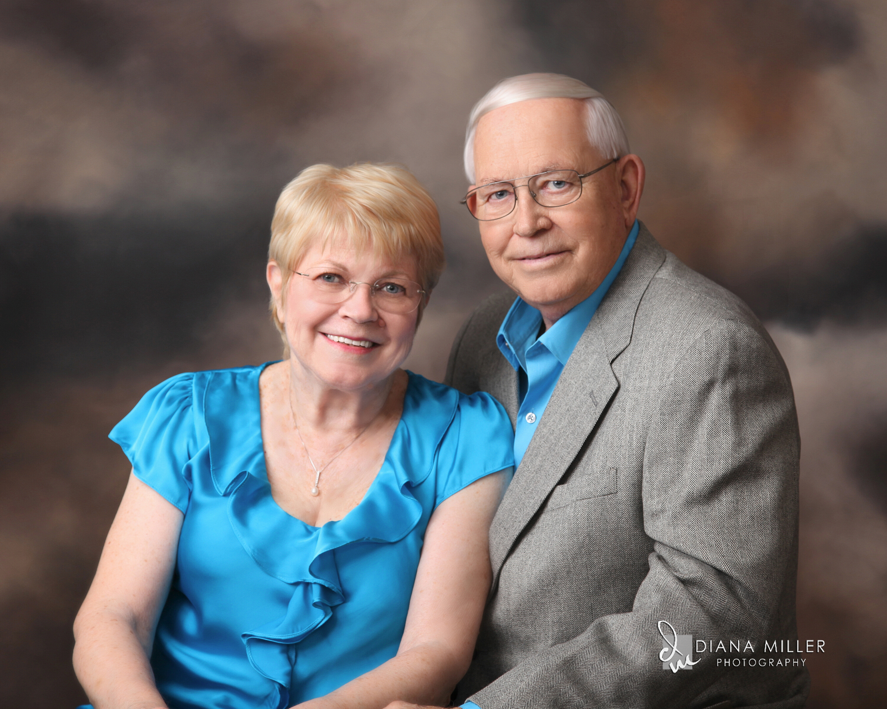 A studio portrait of a senior citizen couple.